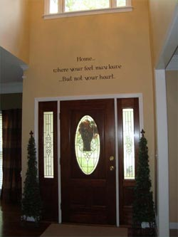Home..where your feet may leave...But not your heart. A wall decal in between the window and the main entrance door with 2 indoor plants on both sides of the door.