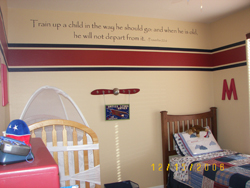 Train up a child on the way he should go and when he is old, he will not depart from it, a wall decal on the center of the wall above the red and blue wallpaper partition, with crib and bed in the Aviation themed boy's room