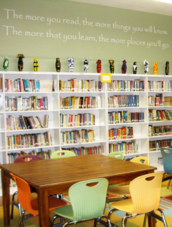 An inspirational wall decal in the library room with books in the shelves and a table with chairs - the more you read, the more things you will know. The more that you will learn, the more places you will go.