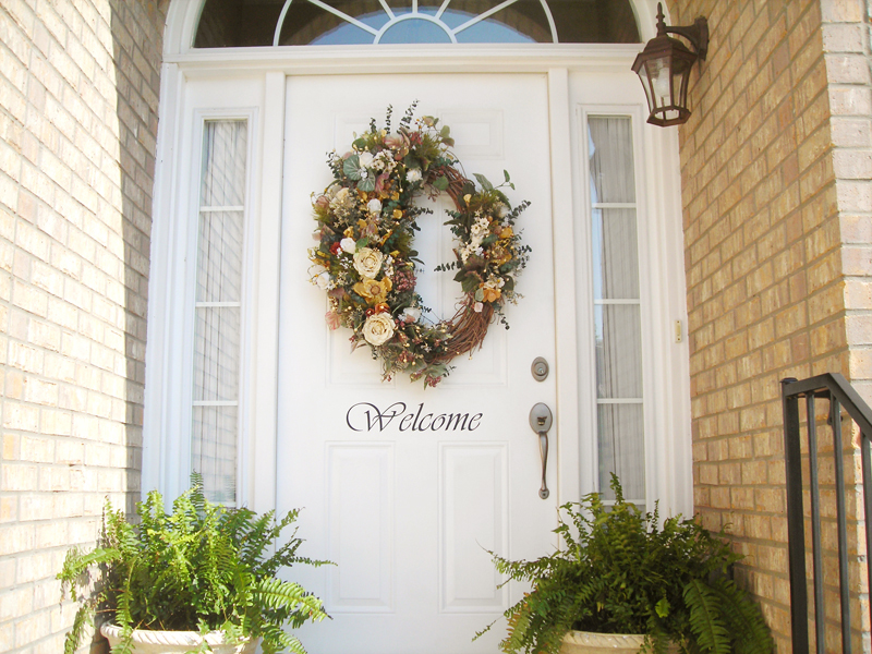A White Colored Front Door With A WELCOME Word And An Ornamental Flower  Decor On The