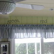Wall words on a green colored wall above the curtain draperies with picture frames beside the window