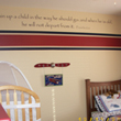 Train up a child on the way he should go and when he is old, he will not depart from it on the center of a wall above the red and blue wallpaper partition, with crib and bed in the Aviation themed boy's room