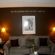 Wall decal on the center of the living room above the sofa with 2 lampshades and a picture frame.