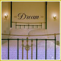 bedroom wall lettering above metal framed headboard in bedroom