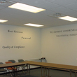 Different wall decals surrounding the 2 corner wall with chairs and tables in the board room