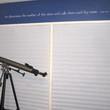 Bible verse decal above a window and beside a telescope in a stars and astrology themed boy's bedroom
