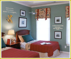 kid's room wall decal above bedside lamp and between wall photos in kid's flying room