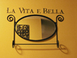 Charming Entrance.La Vita E Bella - wall lettering above the black colored wall decoration.