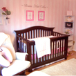 Wall quotes on the center of a baby girl's room, above the 2 wall picture frames and a wooden baby girl's crib