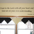 A wall decal quote from the bible above the window with colors white and dark brown drapery.