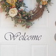 A white colored front door with a WELCOME word and an ornamental flower decor on the center.