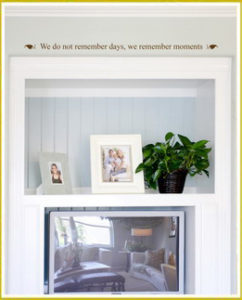 photo wall quote decal above recessed white cabinet with photo