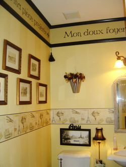 A french wall quote in the toilet room with picture frames on the left side and a lavatory with water closet on the center
