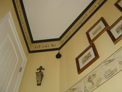 Wall decal near the ceiling with a door on the left side and photo frames on the right