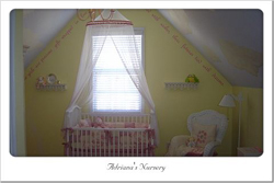Wall inscriptions just below the ceiling in this pastel motif nursery room with a crib and a hanging crib curtain on the center