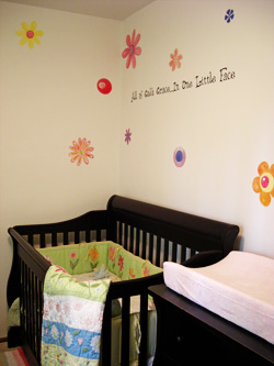 A wall decal in the baby's room with a wooden crib and a drawer -All of God's grace is one little face