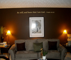 A Bible verse wall decal above the picture frame and a sofa with two lampshades on both sides in the living room - Be still and know that I'am God.