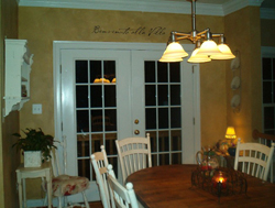 Benvenuto Alla Villa wall decal above the colonial glass paneled door with dining table and chairs in the dining room area