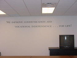 A motivational wall decal in the board room with a table and a television - We improve communication and vocational independence... for life!