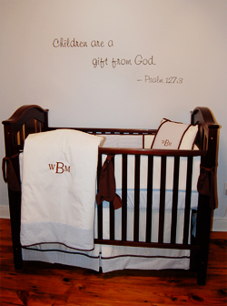 A bible verse wall inscriptions on the center with a wooden baby's crib in the baby's room