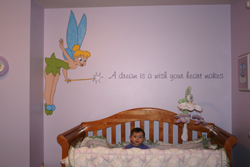 Cutie Pie and her Dream beside Tinkerbell with her magical wand on the center of a lavender wall with a baby crib in the baby's room. A Dream is a wish your heart makes