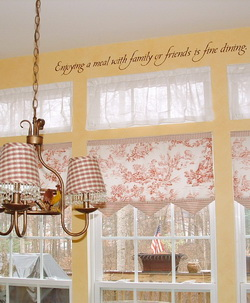 A wall decal in the dining room above the dining windows with chandelier on the center - Enjoying a meal with family or friends is fine dining.