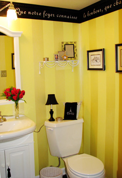 A french wall quote right below the ceiling with water closet and a lavatory in this french-yellow inspired toilet room
