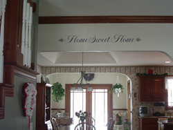 Home Sweet Home wall quotes with a fancy end lettering art on the wooden beam in the kitchen area.