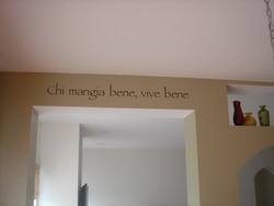 An Italian wall decal on the drop beam ceiling with 3 bottles on the right side - Chi mangia bene, vive bene