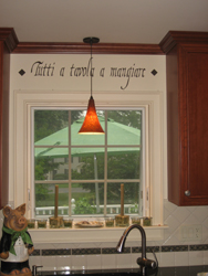 An Italian kitchen wall quote above the kitchen window and in between the kitchen wall cabinets, with kitchen sink and a pendant