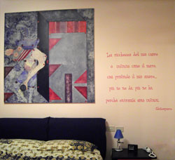 An Italian Shakespeare wall quote on the bedroom with the bed and the painting in the side.