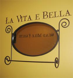 Charming Entrance.La Vita E Bella - wall lettering above the black colored wall decoration.