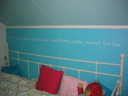 A wall lettering in the boys attic room with a bed and throw pillows in it