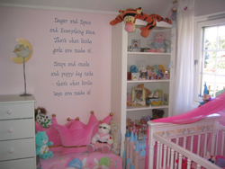 Wall quotes in between the dresser and accessory shelves with a pink baby's crib beside the baby's room window