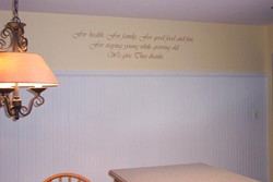 A wall quotation above the table and chair with a chandelier on the left side