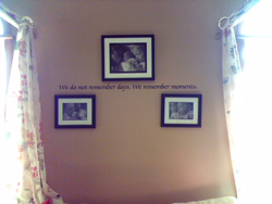 A wall decal in between 2 windows with draperies and 3 family photo frames