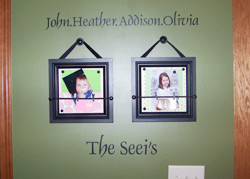 The Seeis a dark green color wall decal with 2 pictures of baby kids on a hallway - John. Heather, Addison, Olivia