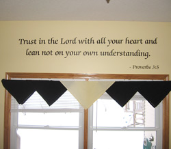 A bible verse wall quote below the window with black and white window drapery