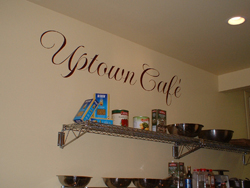 Uptown Cafe wall quote in red colored fonts with accessory shelves.