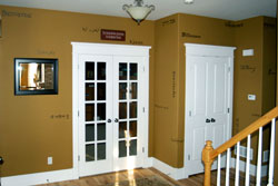 Wall words beside the white colored glass paneled main entrance door with a 1 piece chandelier on the center