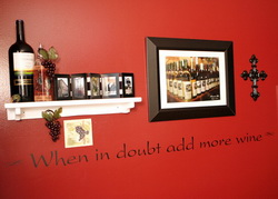 A wall decal on the red colored wall with a photo frames and wines on the display shelf - When in doubt add more wine